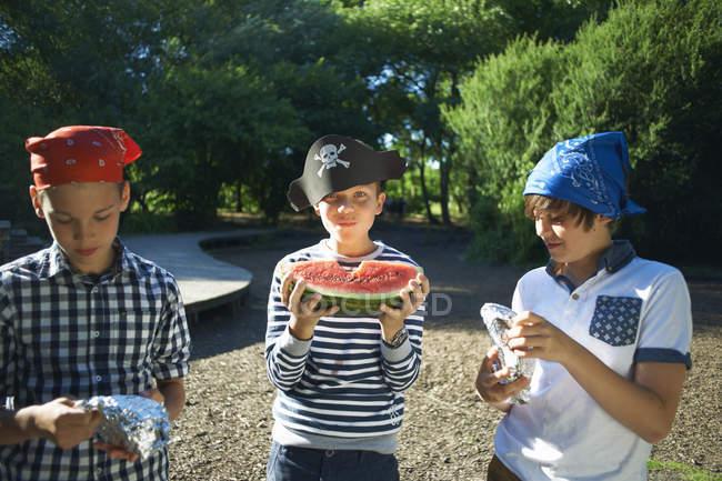 Three little boys having watermelon lunch in park — Foto stock