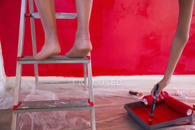 Обрезанный снимок красной стены девушки и матери — стоковое фото