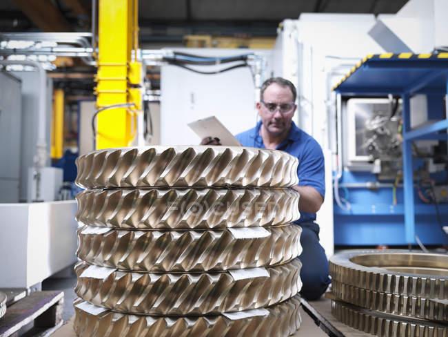 Engineer with bronze cogs in engineering factory — Stock Photo