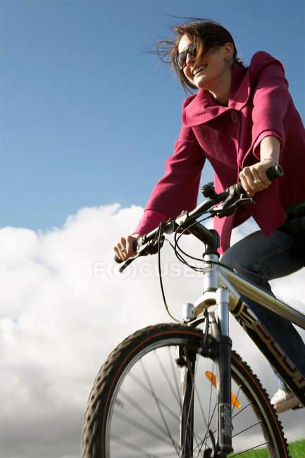 Mujer monta en bicicleta al aire libre - foto de stock