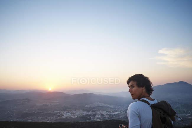 Молодой человек, смотрящий на пейзаж и закат, Хавея, Испания — стоковое фото