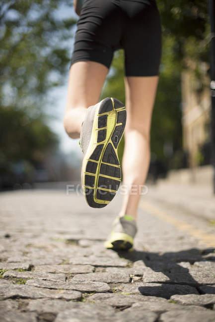Corredor correndo na rua paralelepípedo — Fotografia de Stock