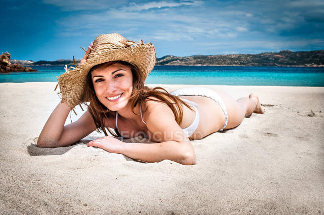 Portrait of young woman wearing bikini and sunhat lying on beach, La Maddalena, Sardinia, Italy — Stock Photo