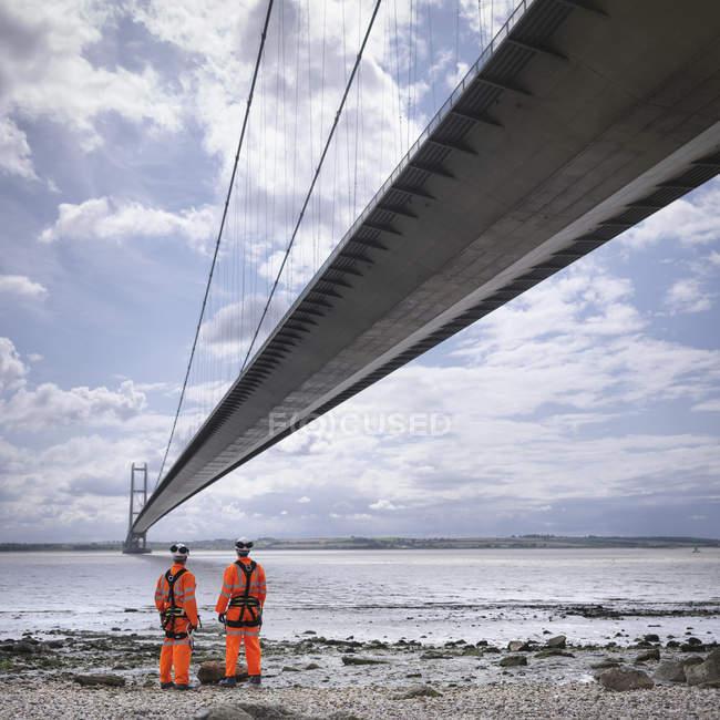 Работники моста на пляже под подвесным мостом, Хамбер Бридж, Великобритания — стоковое фото
