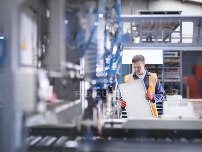 Рабочий осмотр деталей рядом с роботизированной машиной для резки металла на заводе листового металла — стоковое фото