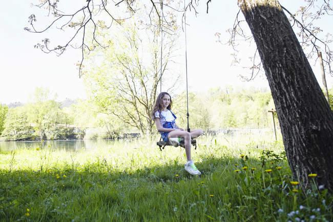 Дівчина сидить на гойдалці в зеленому літньому саду, портрет — стокове фото