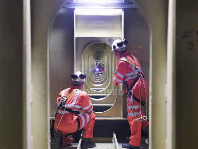 Ingenieros civiles inspeccionando estructuras bajo calzada de puente colgante, East Yorkshire, Reino Unido - foto de stock