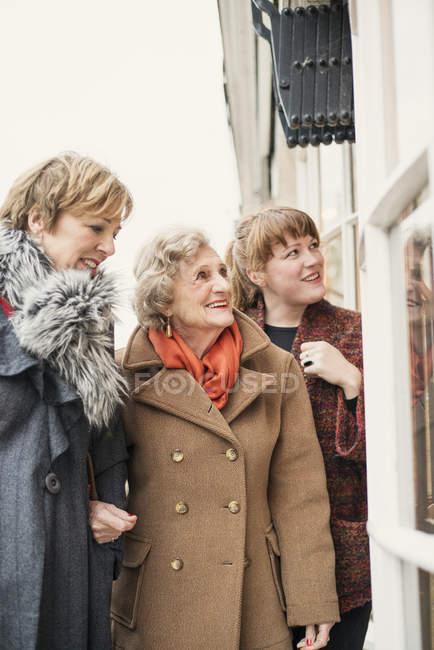 Старша жінка з дочкою і внучкою, дивлячись у вікно — стокове фото