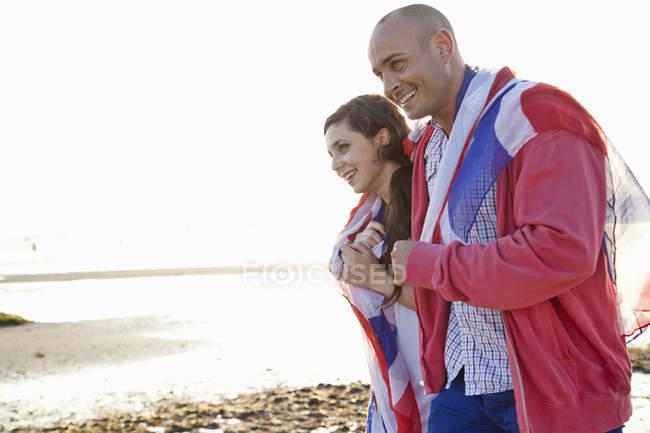 Paar in britische Flagge gehüllt spaziert am Strand von Bourne, Dorset, UK — Stockfoto