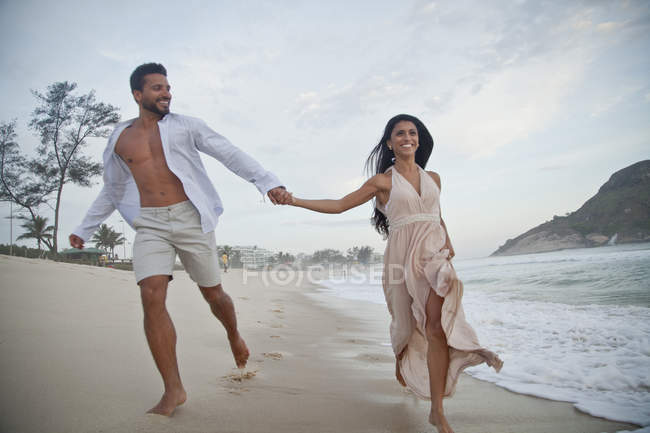 Mid adult couple running along beach, hand in hand — Stock Photo