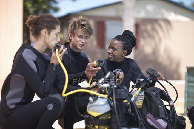 Instructeur de plongée sous-marine démontrant masques à oxygène à des amis — Photo de stock