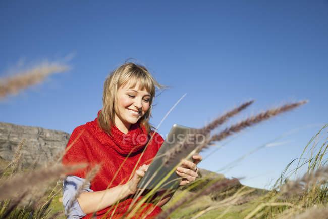 Молода жінка, що сидить у довгій траві, використовуючи сенсорний екран цифровий планшетний — стокове фото