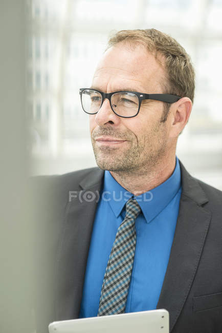 Businessman wearing glasses and looking away — Stock Photo