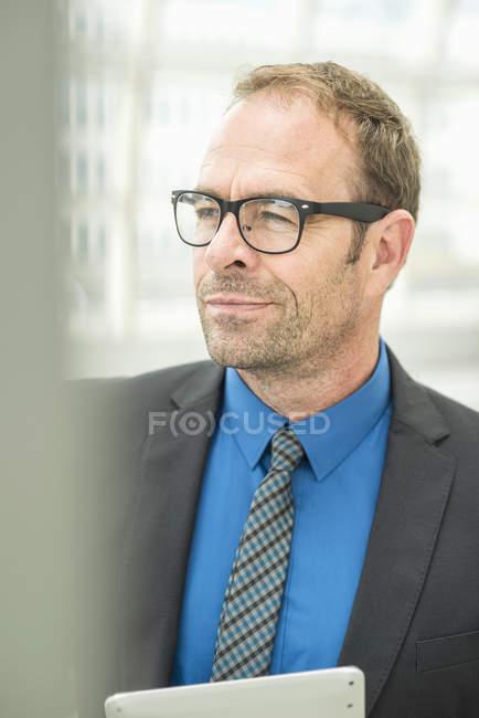 Uomo d'affari con gli occhiali e che osserva via — Foto stock