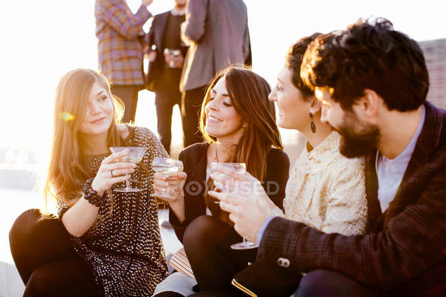 Group of friends laughing and drinking at party at rooftop — Stock Photo