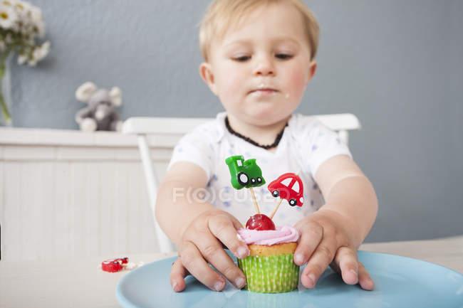 Малыш играет с кексом — стоковое фото
