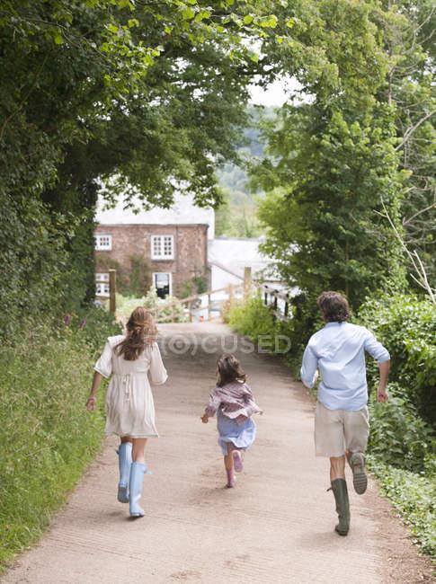Familia corriendo hacia casa de campo - foto de stock