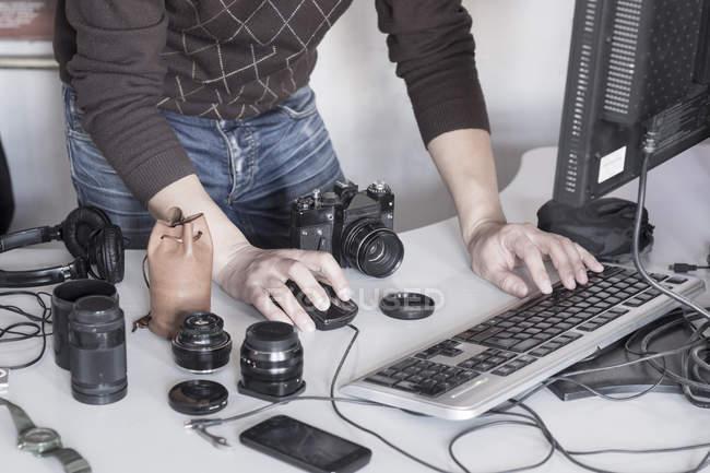 Fotografo maschile che lavora con il computer in studio — Foto stock