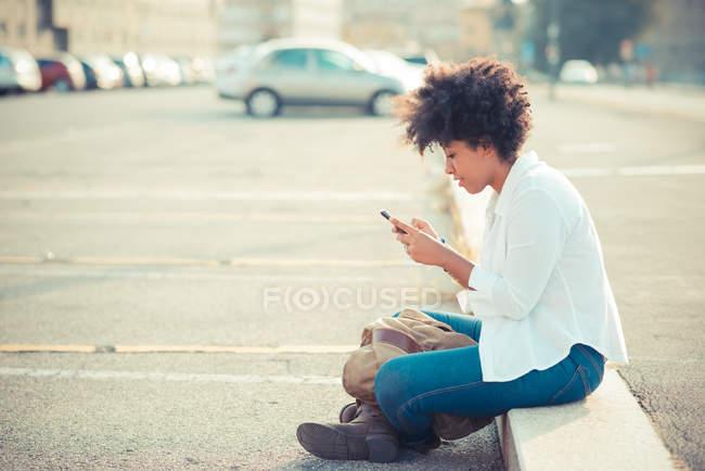 Jeune femme textos sur smartphone dans le stationnement de la ville — Photo de stock