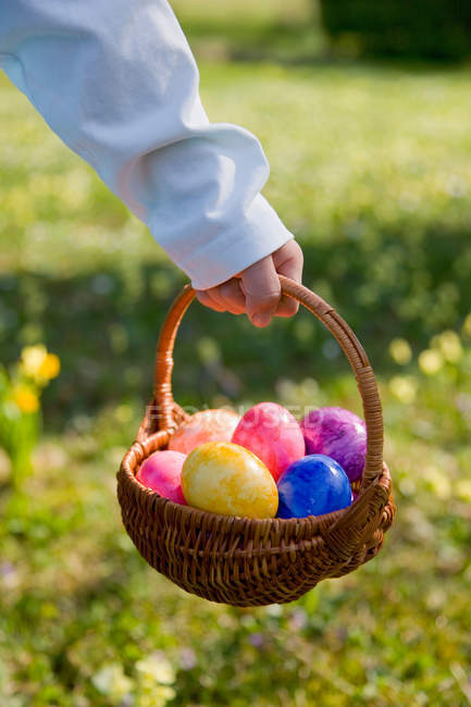Cropped shot of boy holding easter basket with painted eggs — Stock Photo