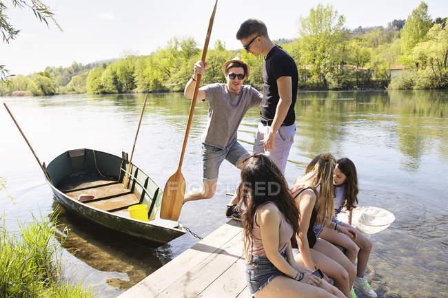Groupe d'amis avec un bateau de ligne sur l'eau et la jetée de fleuve — Photo de stock