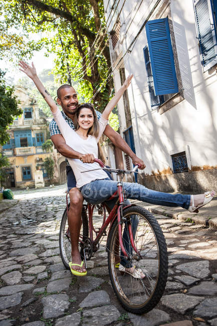 Portrait of couple riding bicycle, Rio de Janeiro, Brazil — Stock Photo