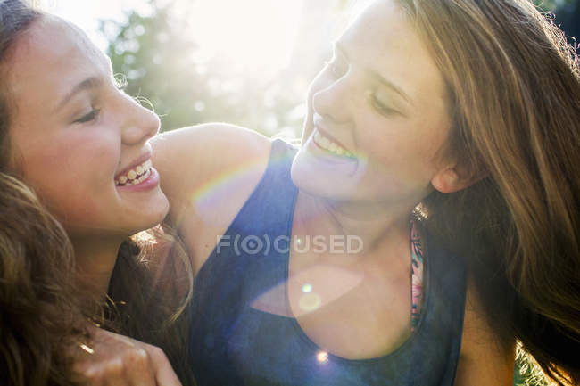 Close up of two teenage girls in sunlit park — Stock Photo