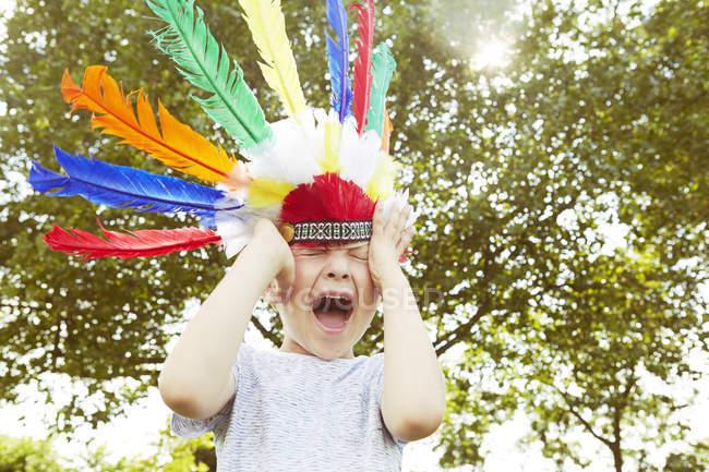 Мальчик в головном уборе кричит в саду — стоковое фото