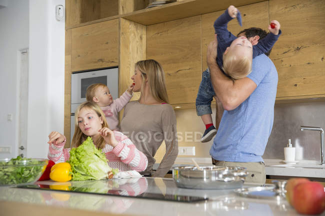 Girl with family preparing vegetables on kitchen counter — Stock Photo