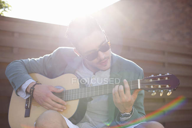 Mid adult man playing guitar at rooftop party — Stock Photo