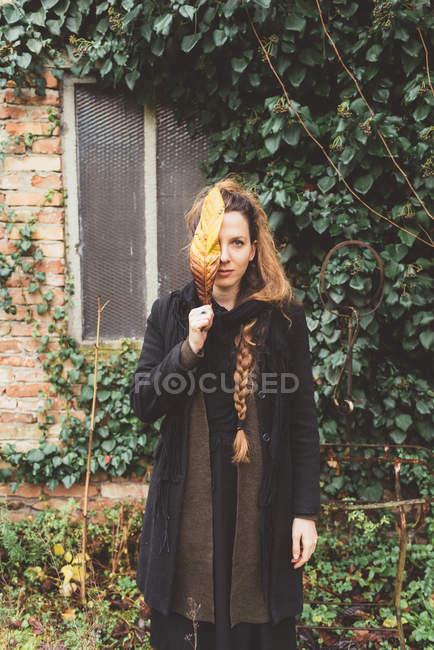 Портрет молодої жінки, що тримає Осіннє листя перед її обличчя — стокове фото