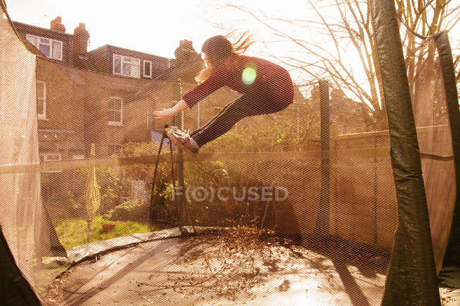Girl jumping mid-air in trampoline in yard — Stock Photo