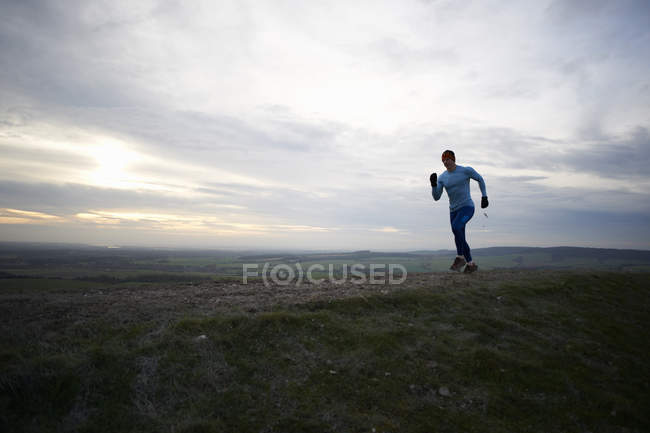 Повна довжина подання впав бігун працює проти драматичні небо — стокове фото