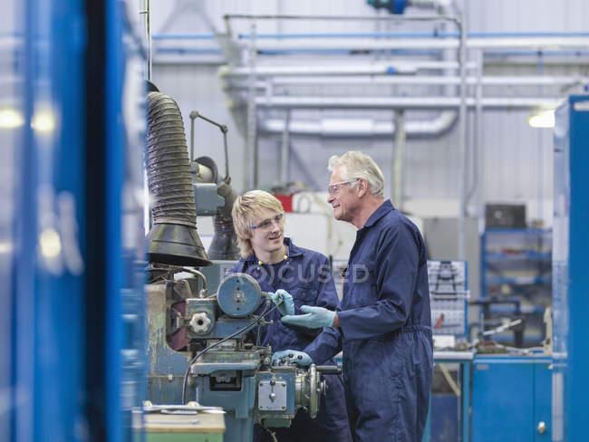 Oberingenieur anweist Lehrling auf Werksmaschine — Stockfoto