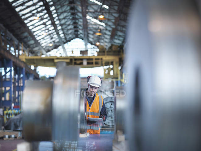 Engineer checking steel parts in engineering factory — Stock Photo