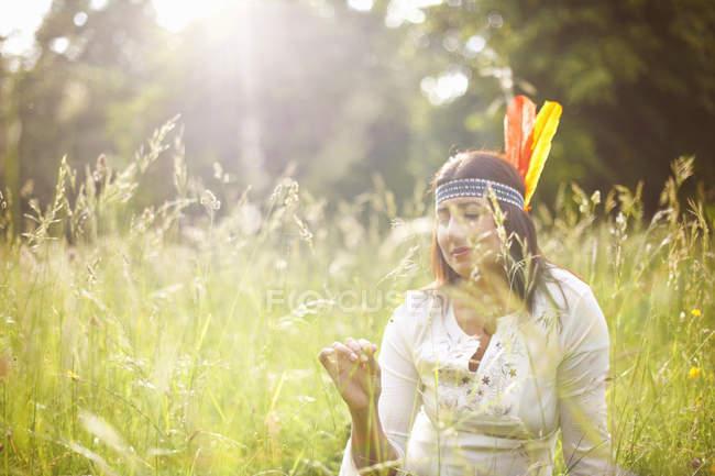 Зрелая женщина в индейском головном уборе в длинной траве — стоковое фото