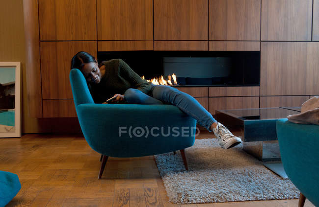 Frau im Sessel vor Holzschränke und offenem Feuer mit smartphone — Stockfoto