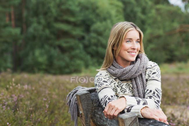 Середині дорослу жінку носити светр на лавці — стокове фото
