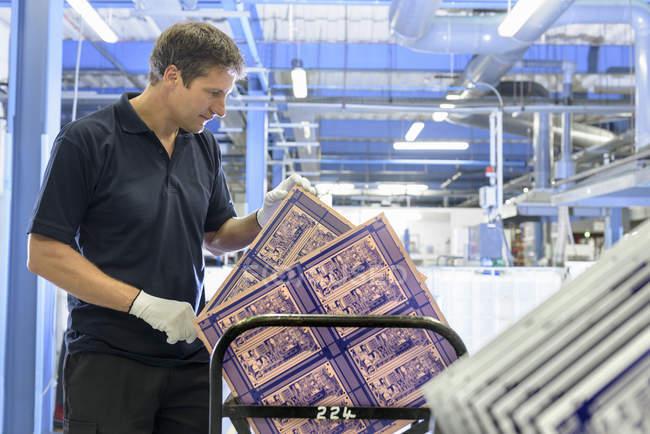 Рабочий осмотр печатной платы на заводе печатных плат — стоковое фото