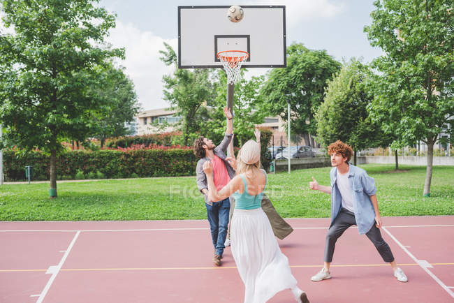 Friends playing basketball  together on court — Stock Photo