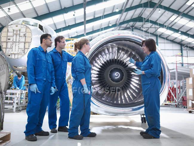 Група інженерів працює над двигуном на заводі технічного обслуговування літаків. — стокове фото