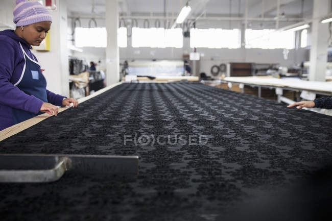 Trabalhadores da fábrica suavizando tecido estampado preto na mesa de trabalho na fábrica de roupas — Fotografia de Stock