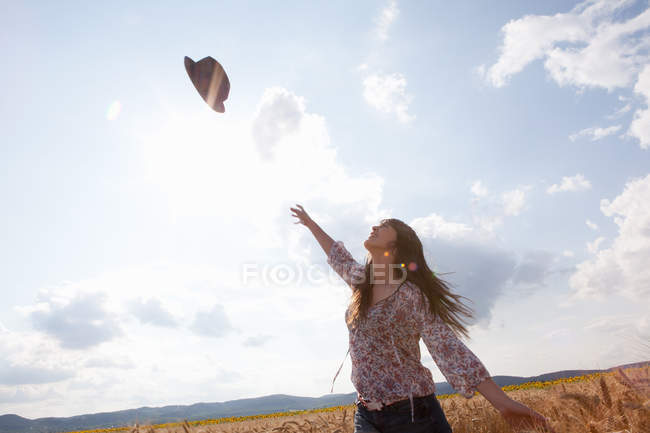 Mid adult woman throwing hat in air — Stock Photo