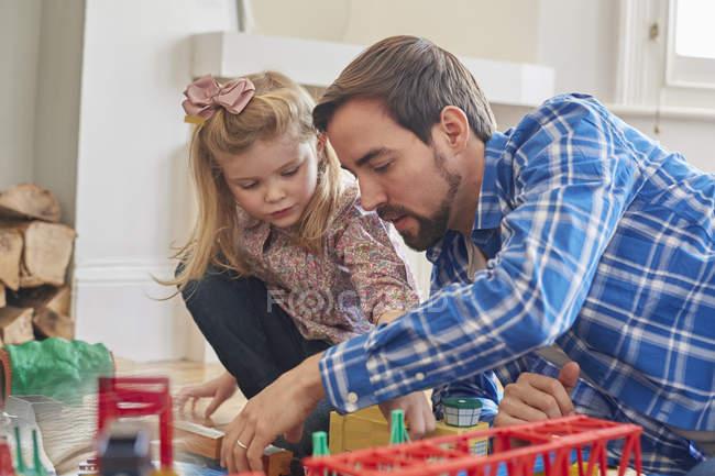 Батько і дочка грають з іграшкового поїзда набір — стокове фото