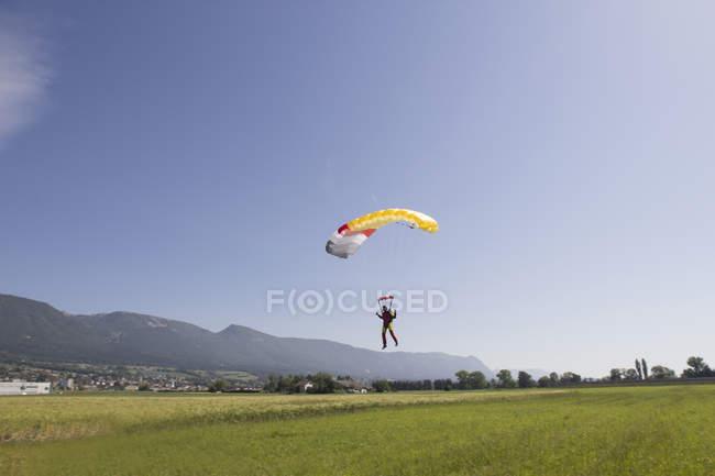 Прыгунья с парашютом, приближается к зоне посадки, Гренхен, Берн, Швейцария — стоковое фото