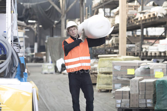 Young male warehouse worker carrying polystyrene roll on shoulder — Stock Photo