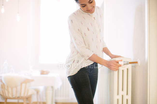 Young woman adjusting radiator switch at home — Stock Photo