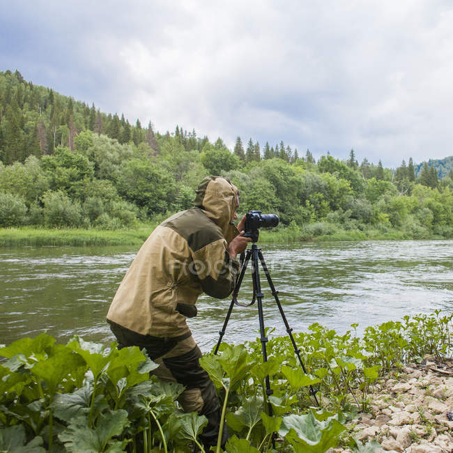 Fotógrafo do sexo masculino fotografando rio rural — Fotografia de Stock