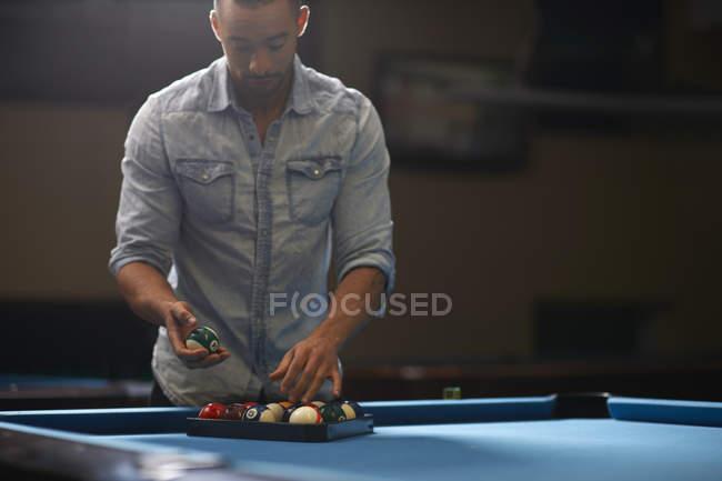 Людина організації кулі в трикутник на більярдний стіл — стокове фото