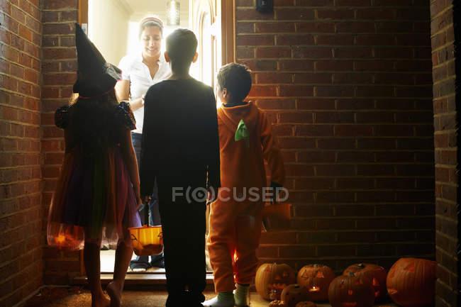 Visão traseira de crianças usando trajes de Halloween truque ou tratamento — Fotografia de Stock